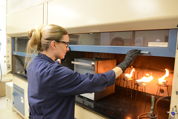Senior Engineer I Rachel Flott analyzes diesel fuel to determine the ash content. The fuel is ignited to allow it to burn until only ash and carbon remain.