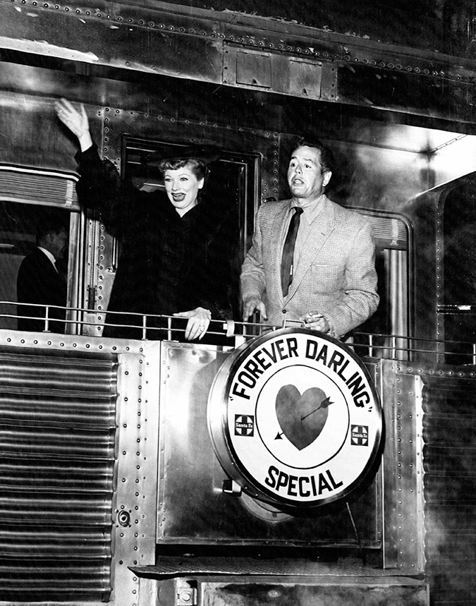Actress and comedian Lucille Ball and her husband actor and musician Desi Arnaz stand on the rear platform of a Santa Fe Railway passenger car in 1956.